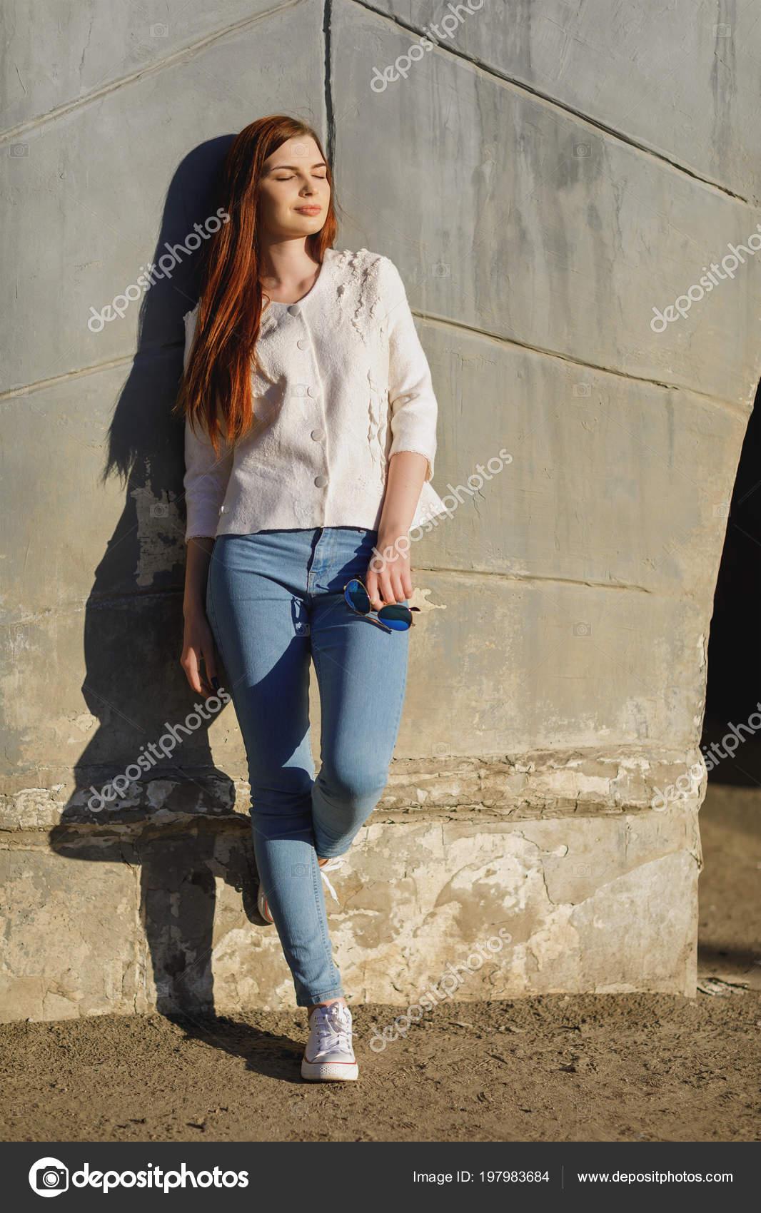 132483d6403609 Concepto sobre el tema de ropa moderna - chica hermosa elegante en una  chaqueta a mano cerca de la pared en una tarde soleada de primavera– imagen  de stock