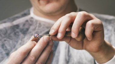 Jeweler fixes stones in a gold ring, close-up