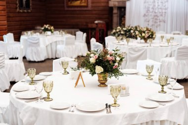 Served tables in white colors for wedding banquet