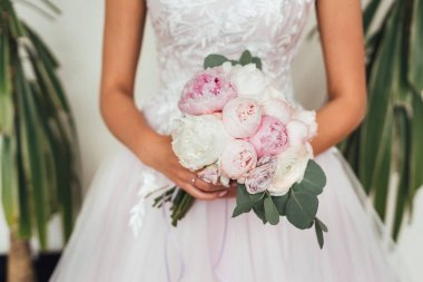 Midsection of bride in wedding dress holding tender bouquet
