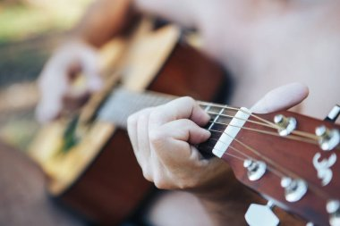 Close up of man hand playing guitar. Man playing guitar. Playing on acoustic guitar outdoor