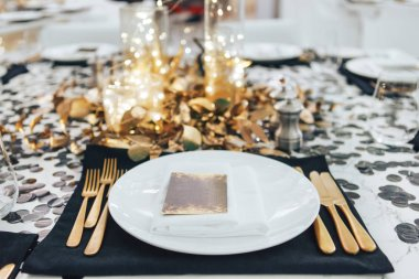 Dinner tableis decorated in black and gold. Garland in a glass flask. Golden fork and knife