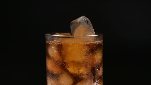 Glass cup with ice and drink on black background.
