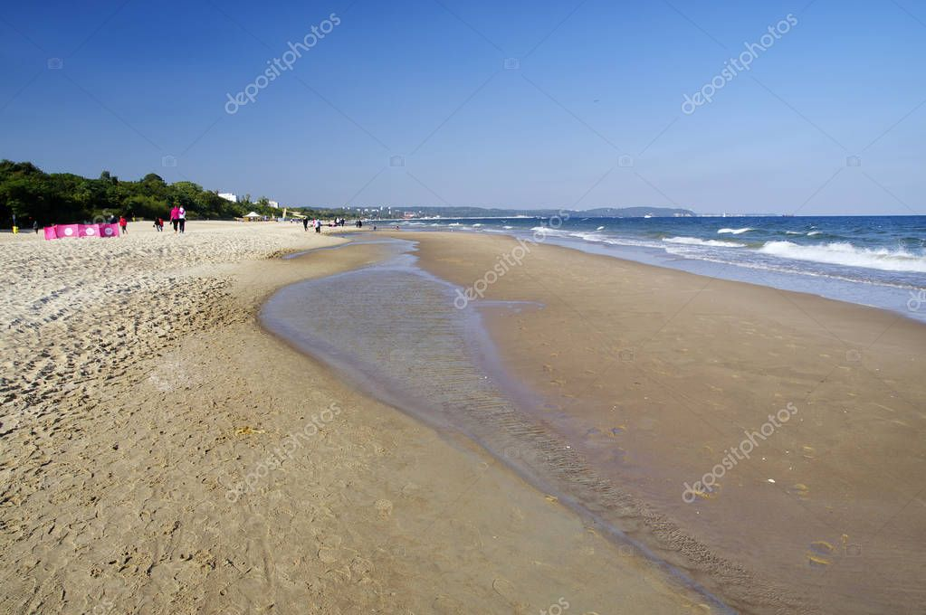 GDANSK,POLAND: SEPTEMBER 30, 2017 : People on the sunny beach of Baltic Sea in Gdansk Brzezno. Gdansk is very popular tourist destination for holidays at Baltic Sea in Poland.