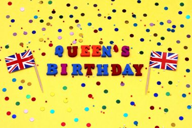 text - birthday of the Queen in bright letters, decorated with colored stones on a yellow background