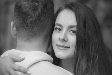 Young beautiful girl gently hugs a man standing ass. Black and white photography
