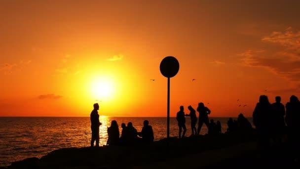 Emberek sziluettje naplemente