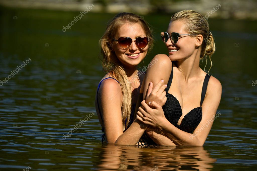 Summer lifestyle portrait of two pretty girls friends having fun in the water.