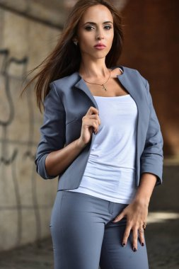 Glamor young brunette woman posing on the city street wearing elegant fashionable outfit.