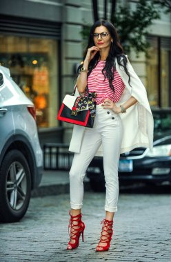 Beautiful sexy young brunette girl with long wavy hairs thin slender figure perfect body and pretty face make-up wearing trendy outfit and accessories walking on the street.