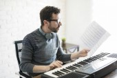 Photo Handsome young man reading music sheet while playing piano