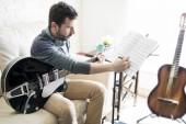 Photo Hispanic man at home studio adding notes on music sheet while composing a new tune