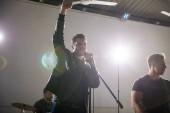 Zpěváka s mikrofon a rock and roll kapela hard rockové hudby na jevišti