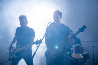 Two male guitarists playing guitar with stage lights and smoke
