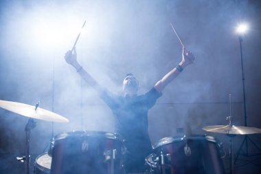 Rock band drummer raising his arms on stage with light and smoke