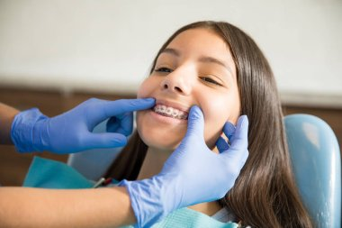 Teenage girl with braces being examined by dentist wearing gloves at clinic