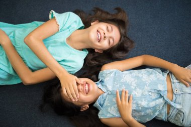 top view of happy little sisters having fun and laughing while lying on carpet