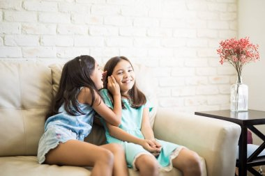 Cute girl sitting on couch in living room and expressing surprise while listening to gossip told by her sister