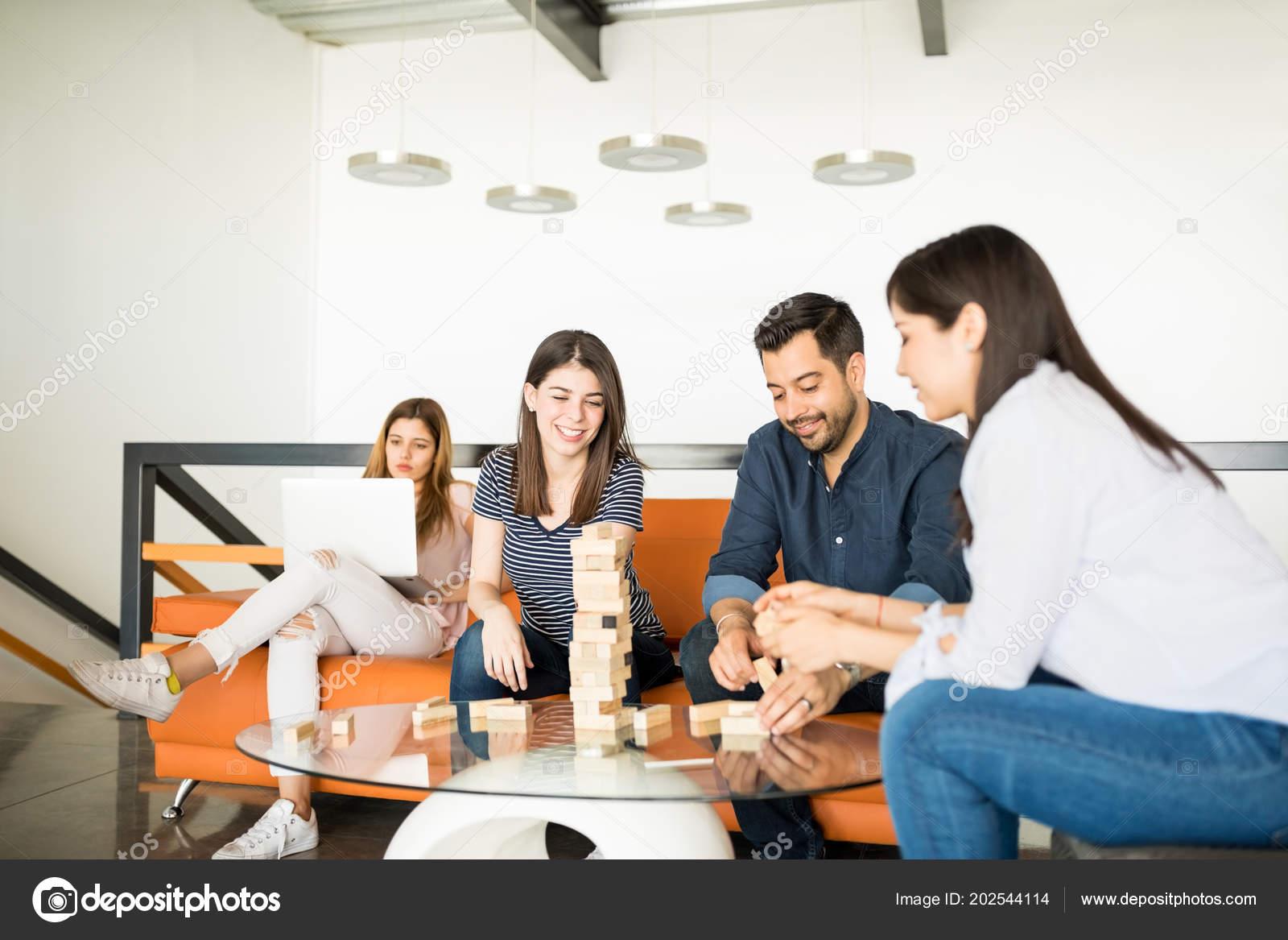 Groupe jeunes gens jouant jenga tout Étant assis bureau salon