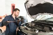 Közepén felnőtt férfi mérnök ellenőrzése az autó-motor alatt megszokott fenntartás műhely
