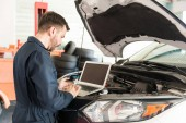 Mid adult auto repair worker using laptop to detect malfunction in car at garage