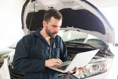 Auto mechanic using computer diagnostic program while repairing car in workshop