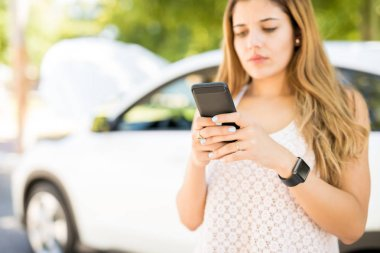 Woman standing by broken down car parked on the road and texting to roadside assistance for help