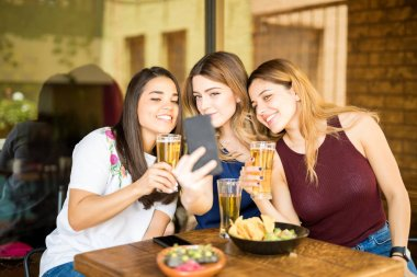 Three young women sitting at restaurant with beers taking selfie with mobile phon