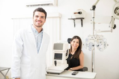 Young optician with pretty woman with tonometer in ophthalmology room for eye checkup