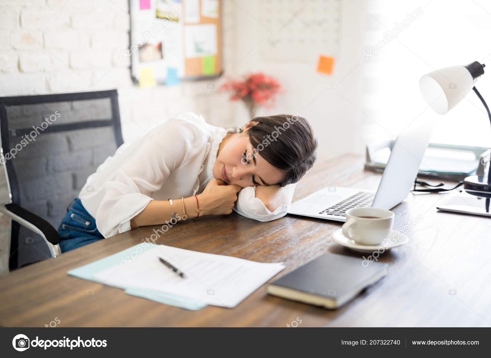Fatigué jeune femme latine dormir sur bureau après longues heures
