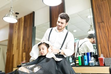 Young barber wiping head of boy with towel in salon
