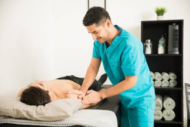 Male physical therapist massaging the injured shoulder of male athlete in hospital