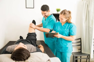 Young physical therapists checking patient's leg and preparing notes in hospital