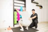 Mladí fyzikální terapeut pomáhá zralý muž dělá dřepy v klinice