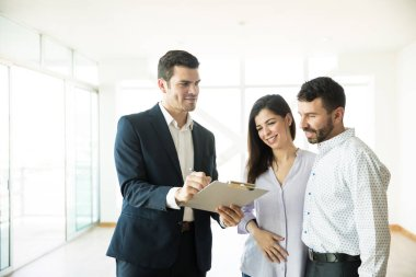 Real estate agent showing contract to couple in new house