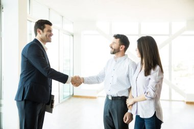Mid adult estate agent congratulating to couple for buying new house