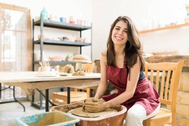 Portrait of female artist making clay pot on pottery wheel in studio