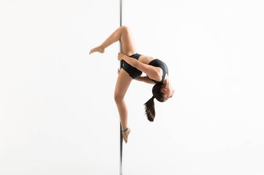 Side view of sensuous woman pole dancing over white background
