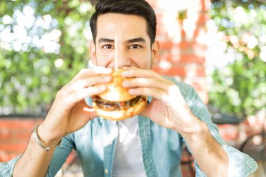 Excited young man eating tasty burger in outdoor restaurant