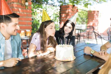 Young Hispanic woman blowing out birthday candles on cake surrounded by friends
