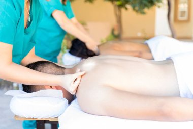 Masseuses giving back massages to husband and wife lying in spa
