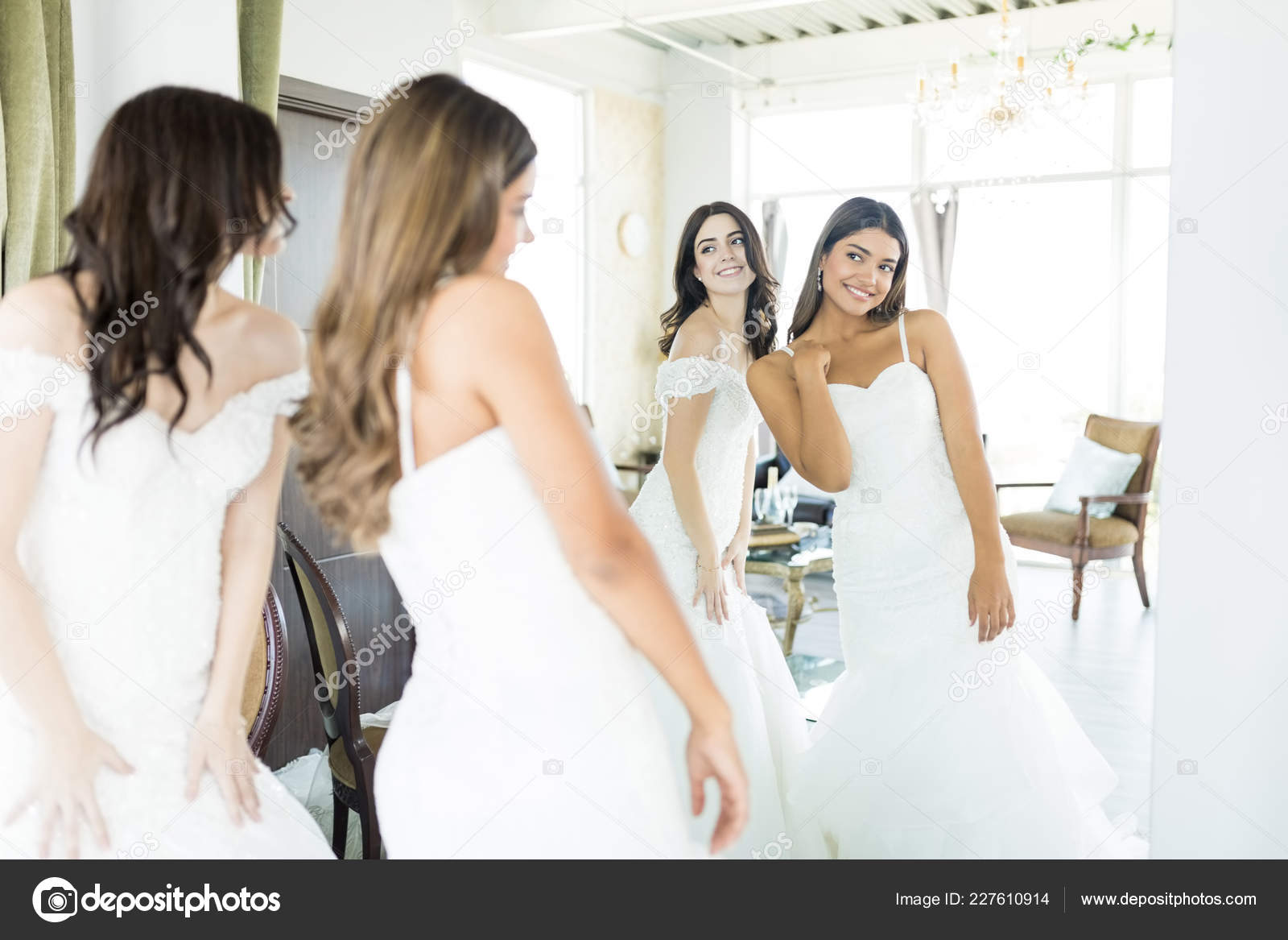 270b00d595a Cute young brides in white dresses looking into mirror at wedding boutique–  stock image
