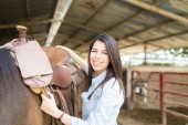 Fotografie Cowgirl tacking up horse by pulling on cinch strap to tighten the saddle at stable