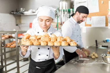Female station chef smelling yummy pastries in restaurant