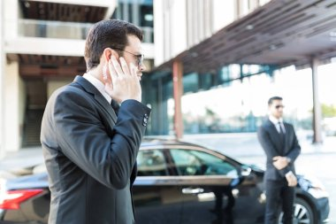 Confident secret service agent listening to updates from security earpiece while waiting by car
