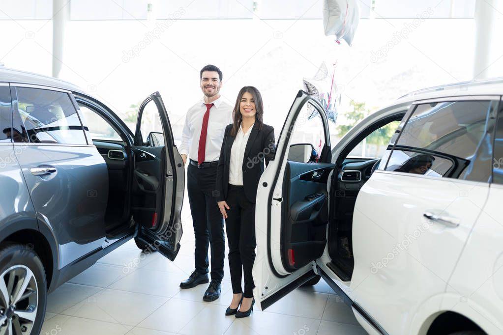 Lunghezza completa dei commercianti professionisti di bell'aspetto che aprono le porte delle automobili allo showroom