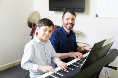 Smiling mid adult instructor enhancing kid's musical skill in extracurricular session