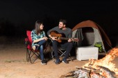 Fotografie Hübscher lateinischen Mann Gitarre von Frau außerhalb camping Zelt in der Nacht