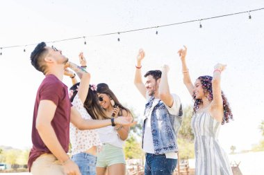 Excited trendy friends dancing at music festival on sunny day