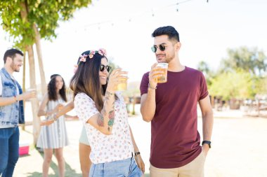 Happy young couple talking while having beer at summer music festival